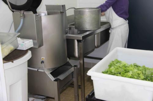 Lucie lave puis essore la salade du jour dans une machine de la taille d'un lave-linge.